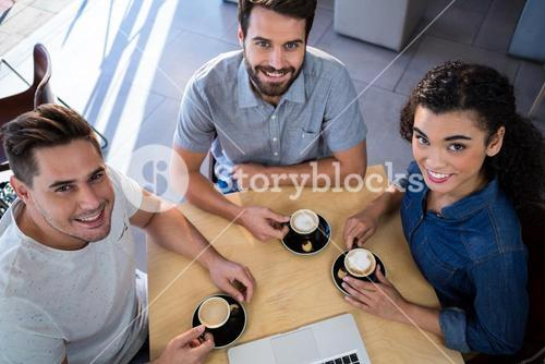 Portrait of smiling friends sitting at a table