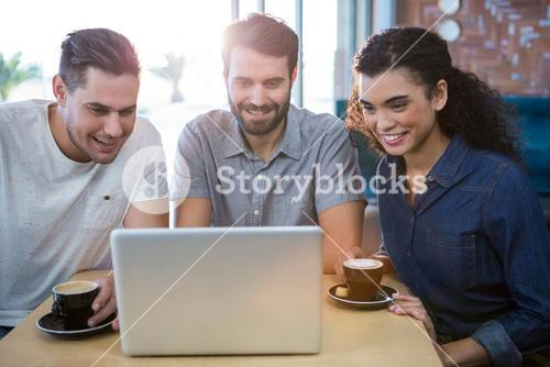 Friends using a laptop in the coffee shop