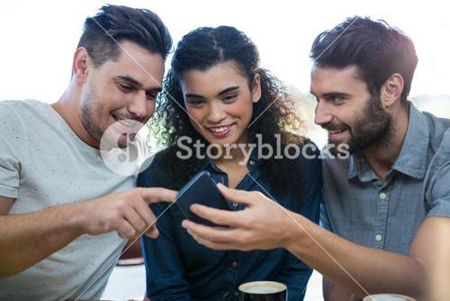 Three friends using mobile phone in the coffee shop