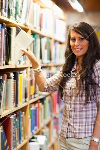 Portrait of a young student choosing a book