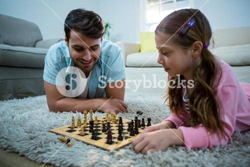Father and daughter playing chess in the living room