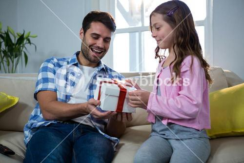 Father giving gift to daughter in the living room