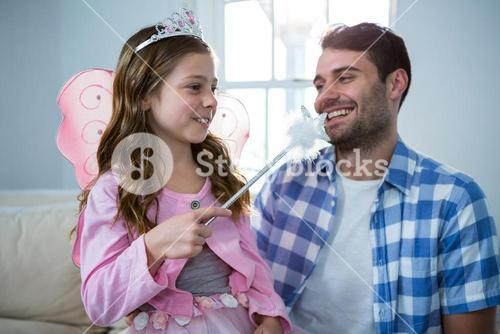 Girl dressed up in a fairy costume interacting with father