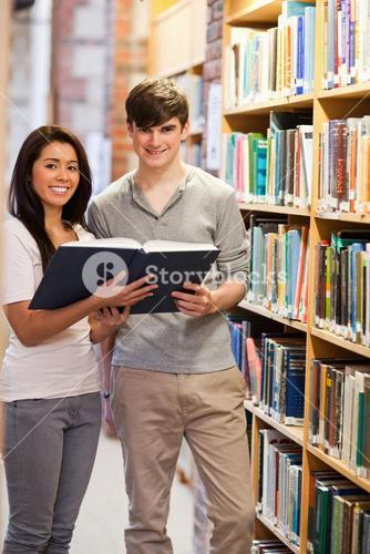 Portrait of smiling students holding a book