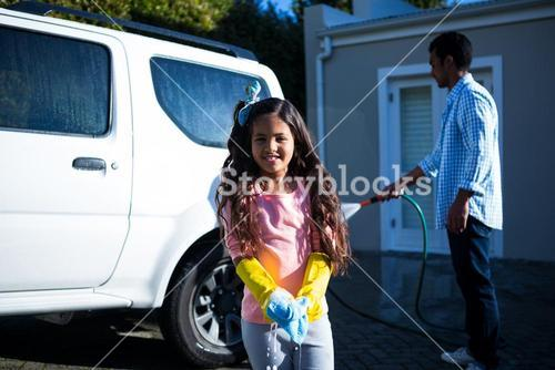 Daughter holding sponge while father doing carwash