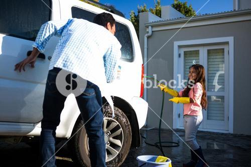 Father and daughter washing car together