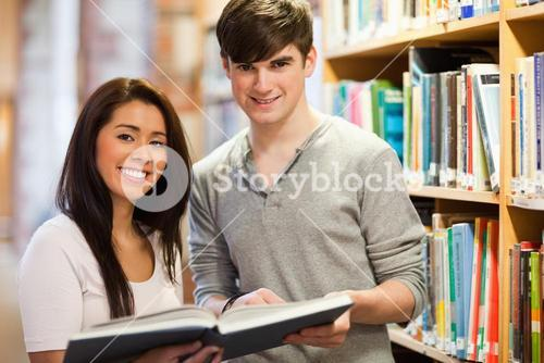 Happy students holding a book