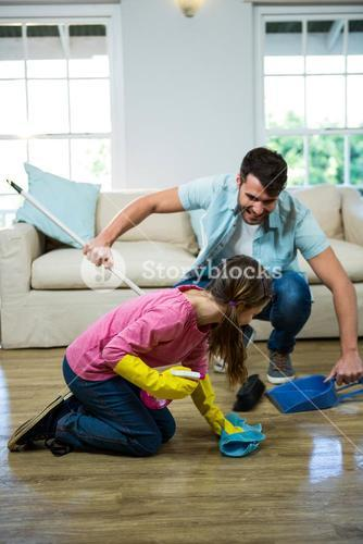 Daughter helping father to clean floor