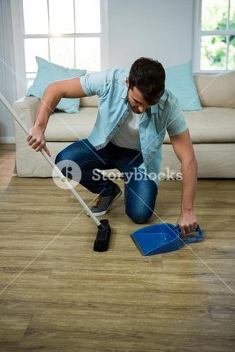 Man cleaning the floor with broom and dust picker