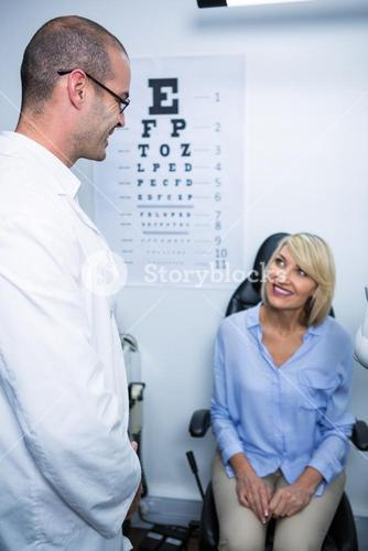 Optometrist interacting with female patient