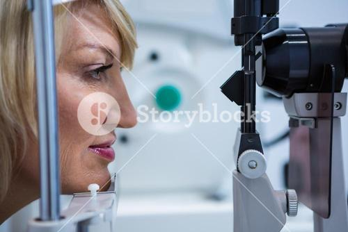 Female patient under going eye test on slit lamp