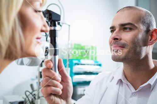 Optometrist examining female patient through ophthalmoscope