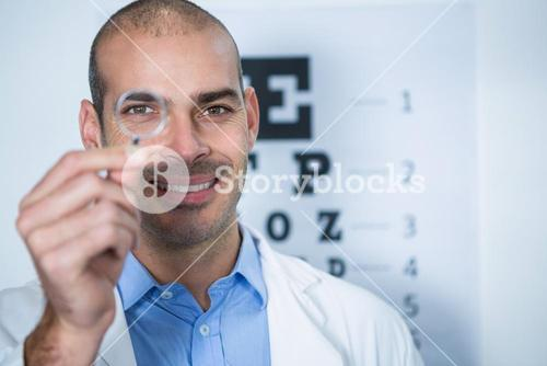 Male optometrist looking through magnifying glass