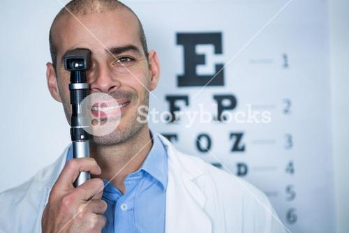 Optometrist looking through ophthalmoscope