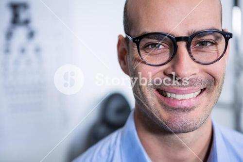 Optometrist wearing spectacles in ophthalmology clinic