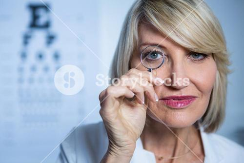 Female optometrist looking through magnifying glass