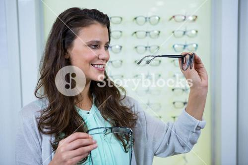 Female customer choosing spectacles in optical store