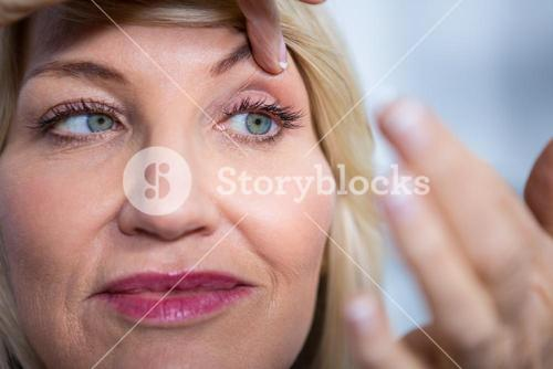 Woman applying contact lens