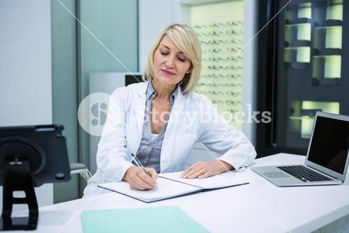 Optometrist writing in book at ophthalmology clinic