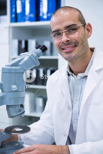 Smiling male optometrist with microscope