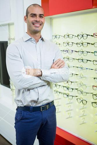 Smiling male optician standing with arms crossed