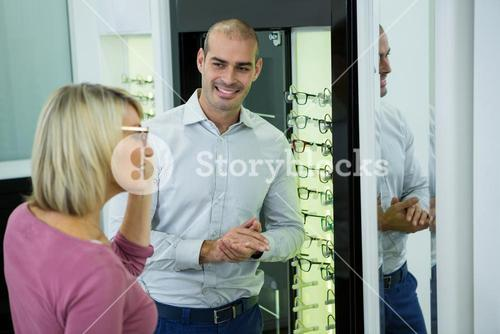 Optician helping customer for selecting a spectacles frame