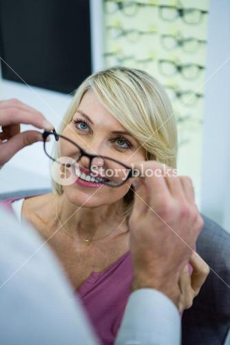 Optician consulting a customer about spectacles and frames