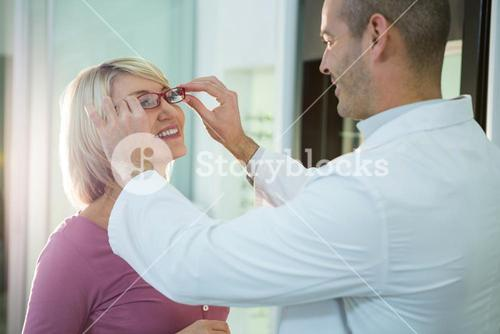 Optometrist consulting a customer about spectacles and frames