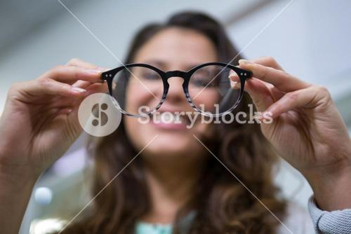 Female customer holding spectacles in optical store