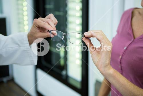 Optometrist giving spectacles to customer in optical store