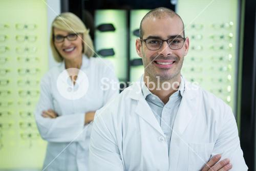 Smiling optometrists standing with arms crossed