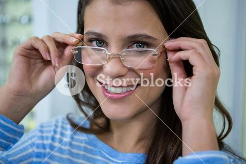 Female customer wearing spectacles in optical store