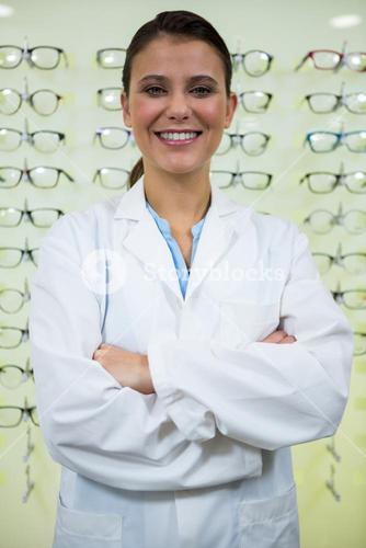 Optometrist standing with arms crossed in optical store