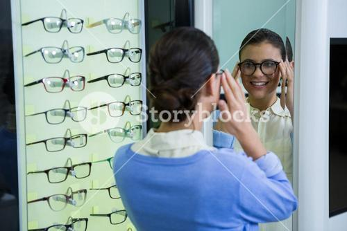 Female customer wearing spectacles and checking in mirror