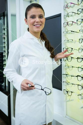 Smiling optometrist holding spectacles in optical store