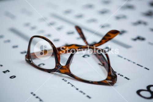 Close-up of spectacles on eye chart