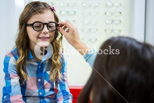 Mother prescribing spectacles to her daughter