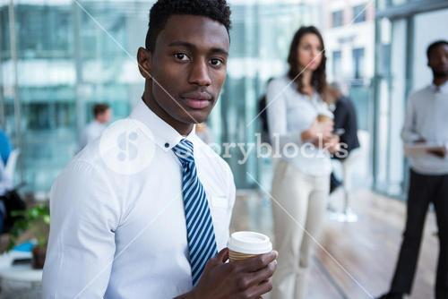Businessman holding coffee in office