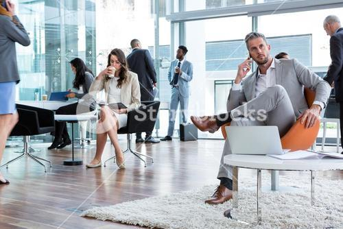 Businessman talking on mobile phone with laptop on table