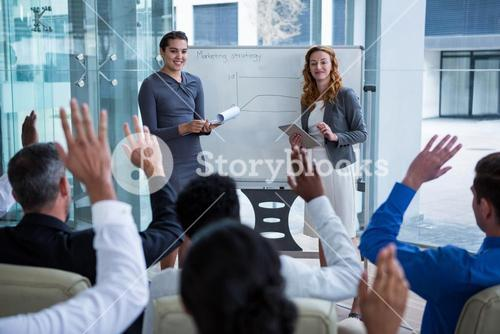 Colleagues raising their hands during meeting