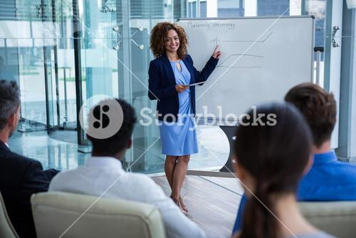 Businesswoman discussing on white board with coworkers
