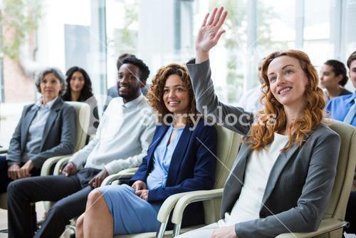 Businesswoman raising hand during meeting