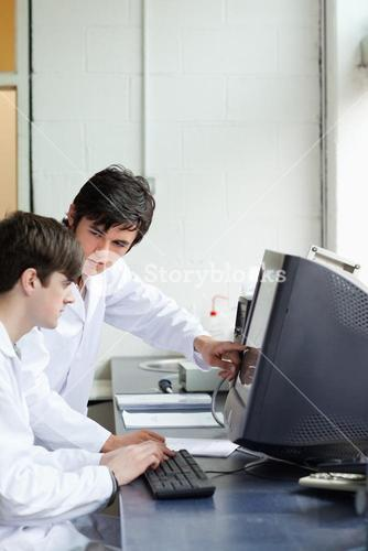Phisician pointing at something on a monitor to his student