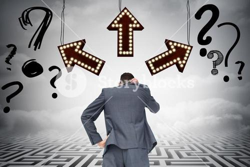 Businessman standing in front of arrows and question marks