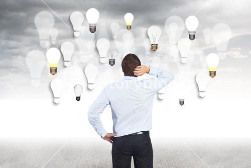 Businessman standing in front of light bulbs