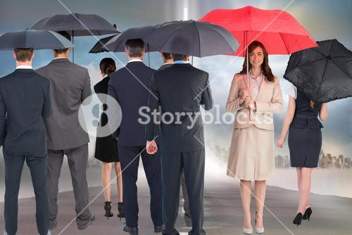 Business people holding umbrellas