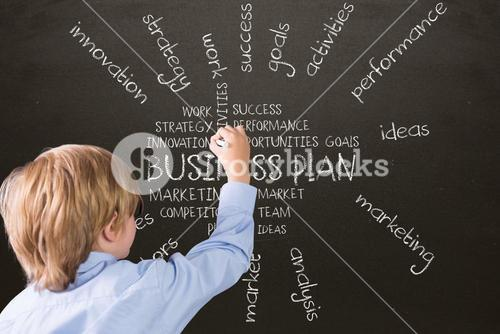 Boy writing a business plan with chalk