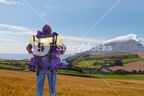 Woman with backpack and hands on hips