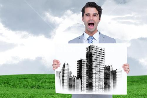 Businessman holding a sign with a city