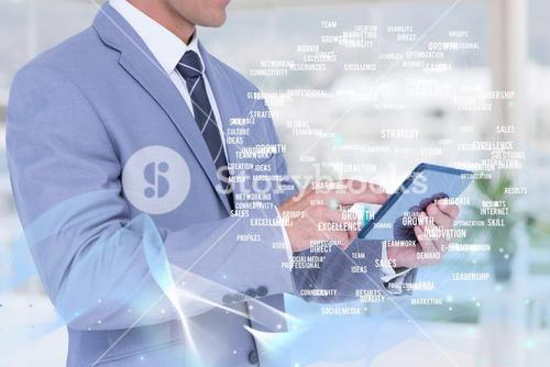 Businessman using a digital tablet with buzzwords hologram